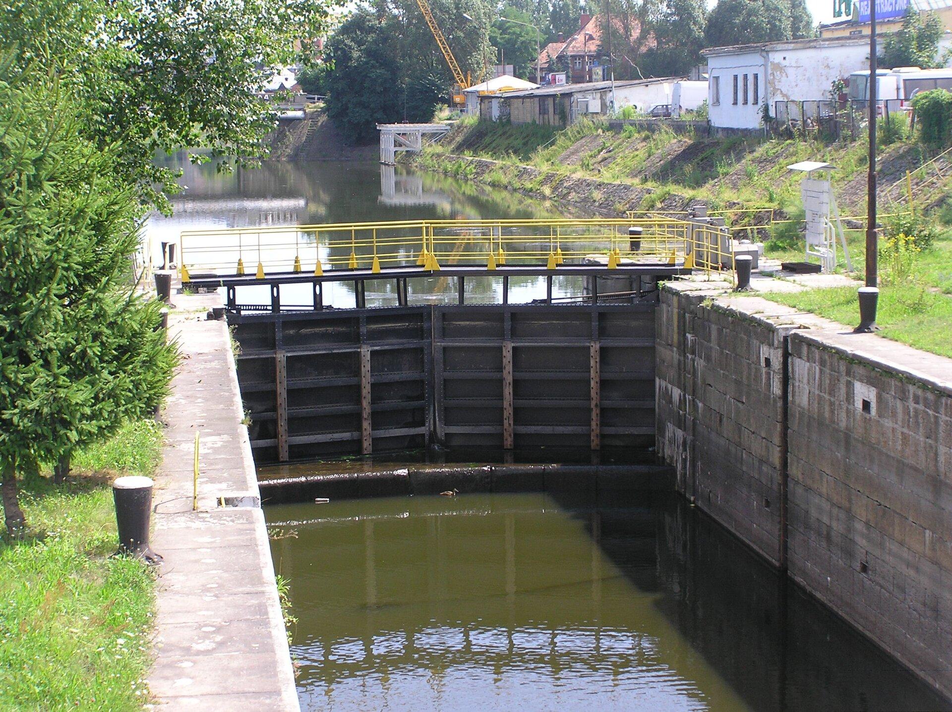 Fotografia prezentuje śluzę na kanale łączącym dwa zbiorniki oróżnym poziomie wody. Śluza skład się zwrót, które zamykają się na kanale, zatrzymując przepływ wody.
