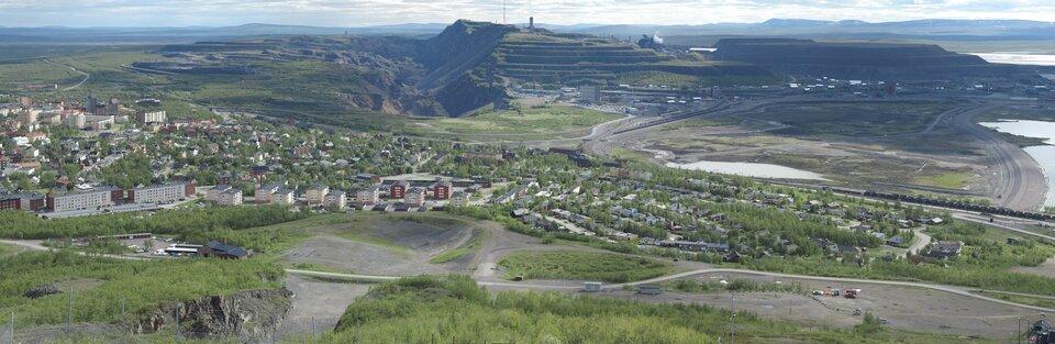 Na zdjęciu na pierwszym planie zabudowa mieszkaniowa wśród zieleni. Dalej kopalnia, rozległe wyrobisko, hałdy, rozjeżdżony teren.