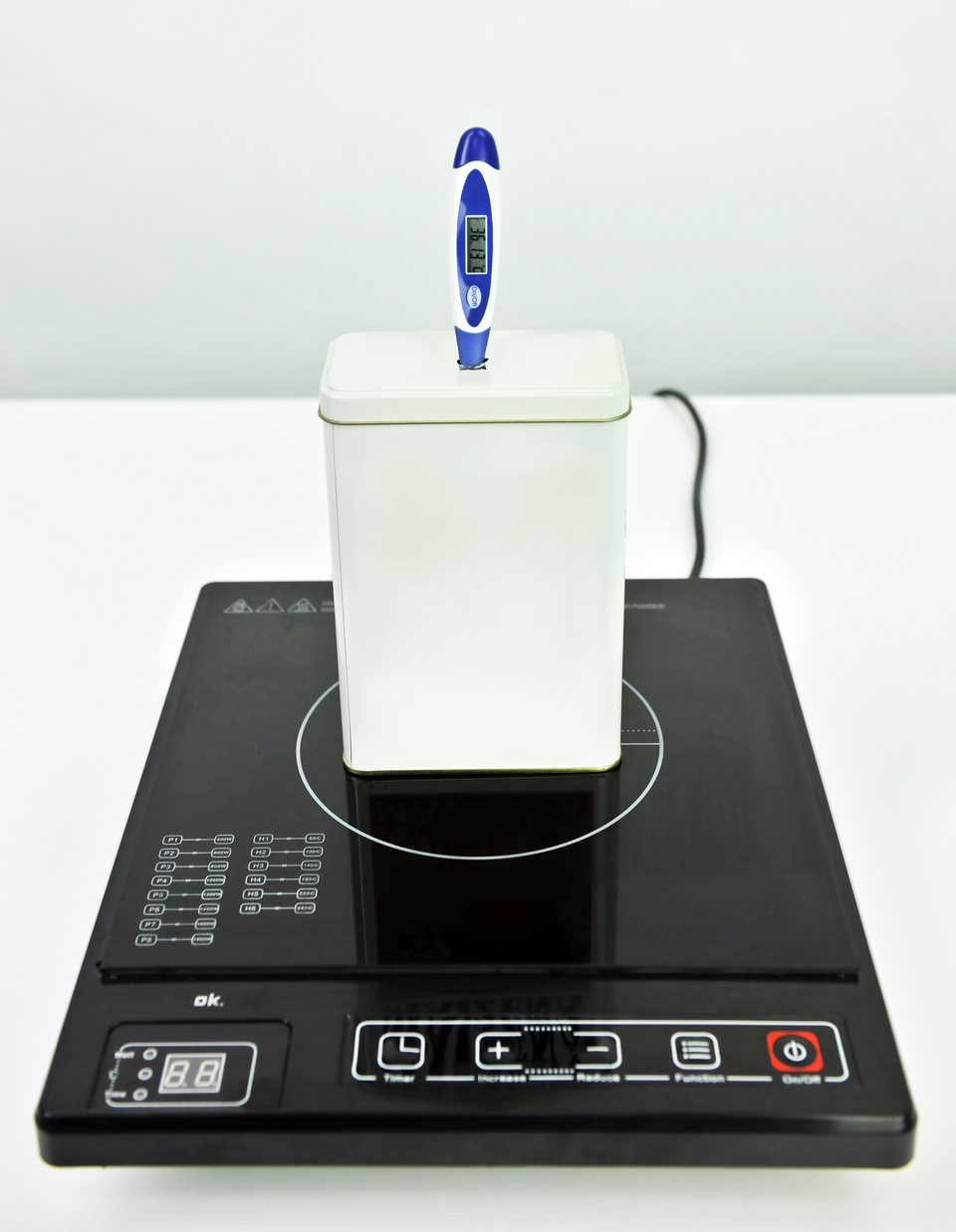 Zestaw naczynie ipokrywa, wktórej znajduje się termometr elektryczny, obok kuchenka elektryczną