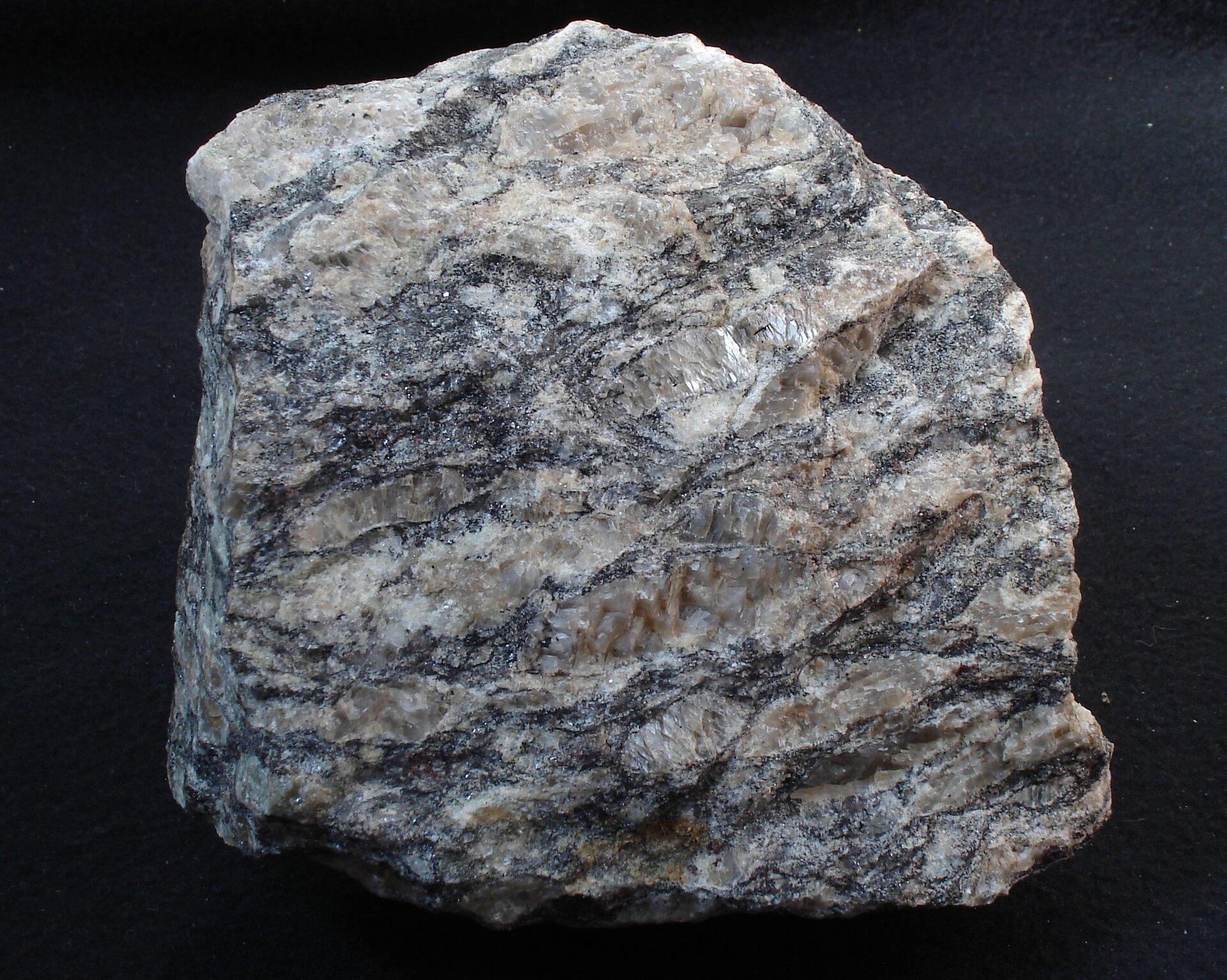 Na zdjęciu przedstawiony jest gnejs – barwa szara, warstwy kwarcowe jaśniejsze różowe, ałyszczykowe ciemniejsze srebrzyste iczarne. Równoległe ułożenie minerałów, tekstura kierunkowa. Fragment skały wielkości pięści.