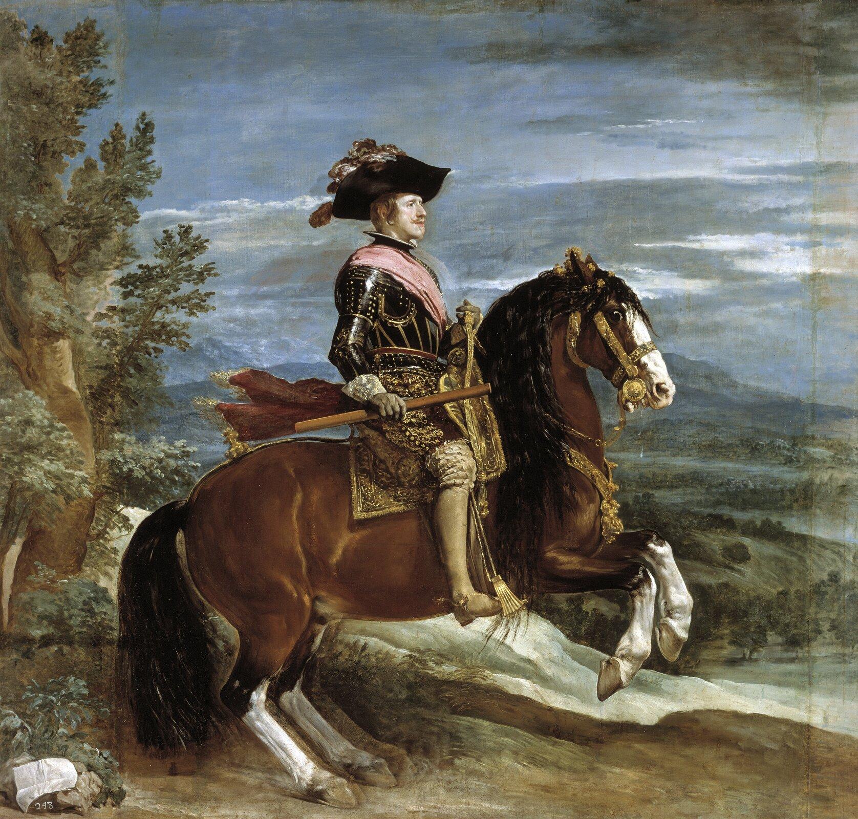 """Ilustracja przedstawia obraz Diego Velázqueza """"Portret konny Filipa IV"""". Dzieło przedstawia mężczyznę zpowagą siedzącego na koniu. Filip IV ubrany jest wczarno-złotą zbroję. Przez pierś ma przewiązaną szarfę, ana głowie założony kapelusz. Zlewej strony obrazu widoczne jest ulistnione drzewo. Wtle, wdolnej partii obrazu widoczny jest daleki krajobraz. Nad nim rozciąga się niebieskie niebo zszarymi chmurami."""