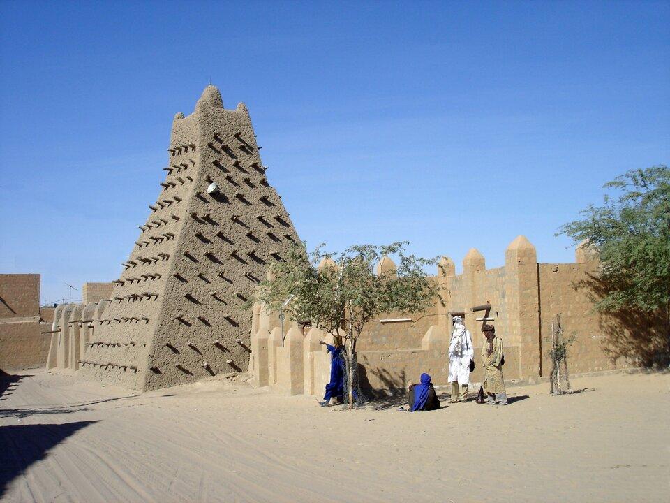 Na zdjęciu gliniana budowla wkształcie graniastosłupa oczworokątnej podstawie, zwężająca się ku górze, wypustki wścianach. Kamienne ogrodzenie, drzewo, ludzie stoją wceniu.