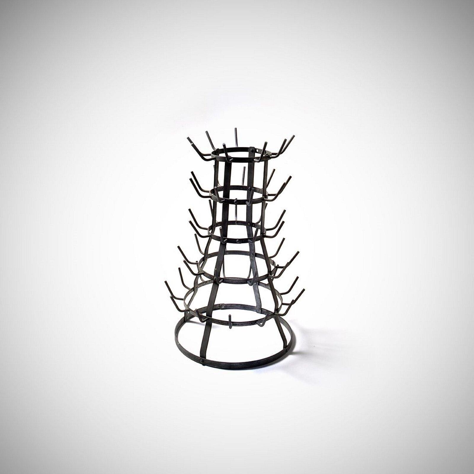 """Ilustracja przedstawia pracę Marcela Duchampa pt. """"Suszarka do butelek"""". Dzieło powstało w1914 roku. Autorem dzieła był francuski malarz kojarzony znurtami kubizmu isztuki konceptualnej. Na ilustracji znajduje się metalowa suszarka na butelki."""