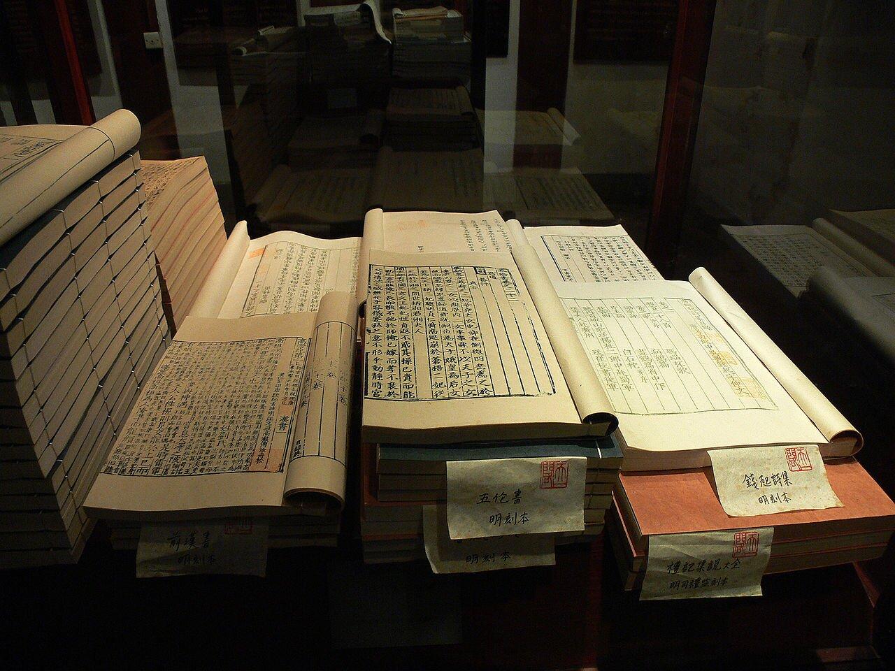 Fotografia przedstawia stosy kartek papieru ułożone obok siebie na stole, które są zapisane chińskimi znakami.