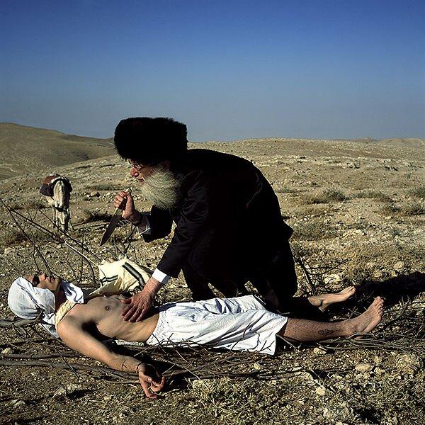 """Akedah Fotografia wykonana przez współczesnego izraelskiegoartystę – Beniamina Reicha,zatytułowana Akedah (2005). Wjęzyku hebrajskim akedah oznacza """"związany, wiążący"""". Źródło: Benyamin Reich, Akedah, 2005, licencja: CC BY-SA 3.0."""