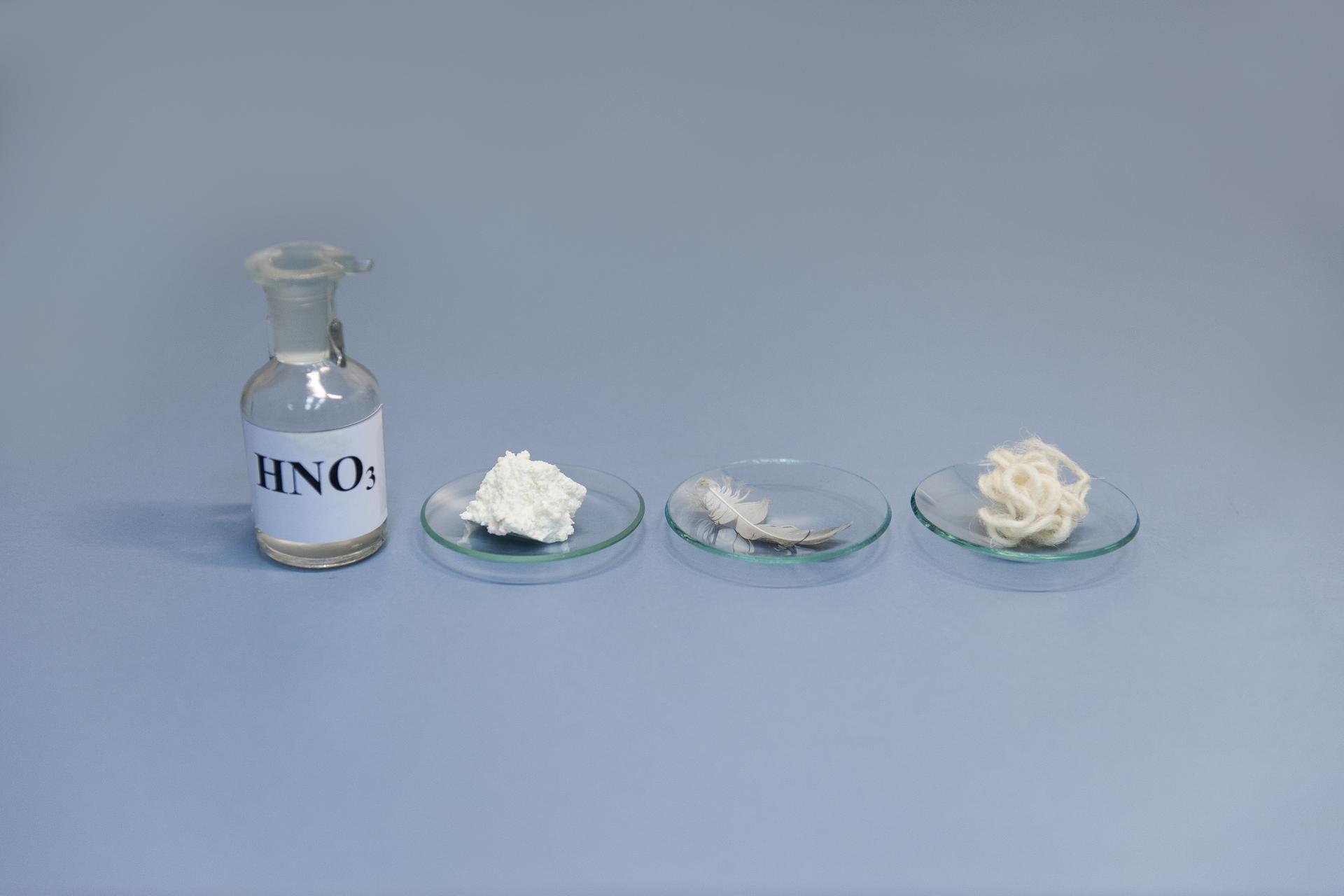 Pierwsze zdjęcie wgalerii. Na ilustracji prezentowana jest szklana butelka zetykietką inapisem HNO3 stojąca na niebieskim podłożu. Po jej prawej stronie na blacie laboratoryjnym stoją wszeregu trzy szkiełka zegarkowe zawierające kolejno: kawałek białego sera, ptasie pióro izwitek owczej wełny.