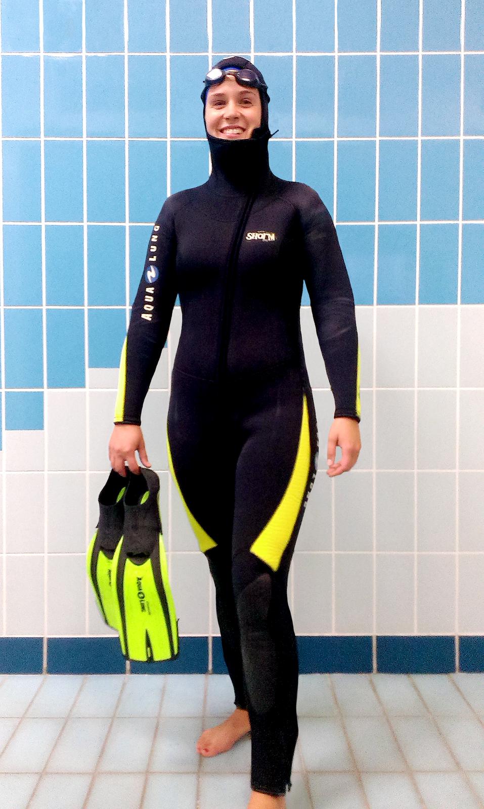 Fotografia osoby wsportowym stroju do pływania - pianka, płetwy, czepek, gogle.