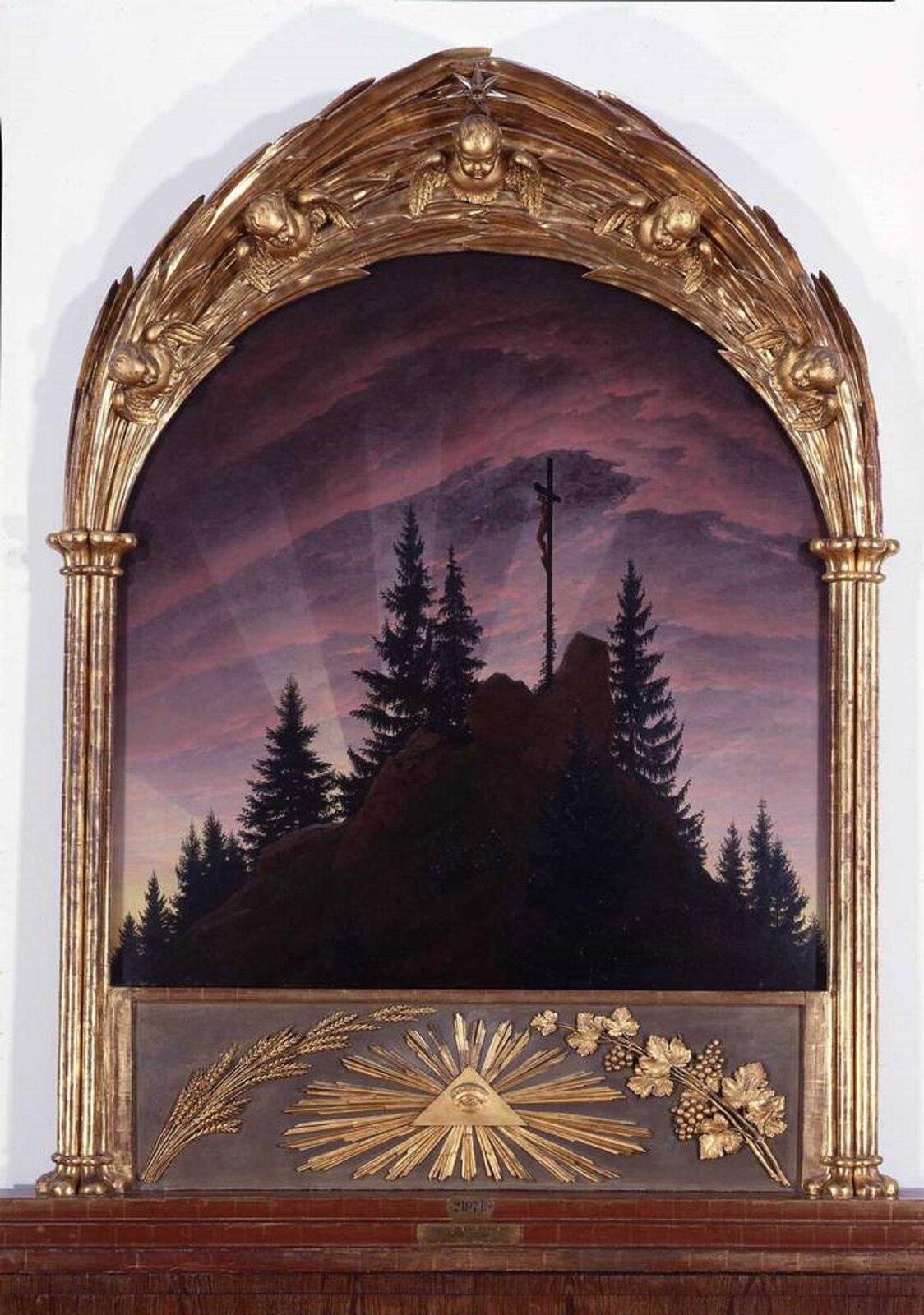 """Ilustracja okształcie pionowego prostokąta przedstawia obraz Caspara Davida Friedricha """"Krzyż wgórach"""". Ukazuje porośnięta jodłami górę, na której szczycie znajduje się krzyż. Niebo wtle to  fioletowo-różowe chmury, rozjaśnione przez trzy słupy światła wychodzące od góry. Obraz znajduje się wzłoconej irzeźbionej ramie , dekorowanej płaskorzeźbami: na dole symbolu Oka Boga zpromieniami iliści, augóry liści lauru, na których osadzone są głowy aniołków ze skrzydłami. Po bokach ramy znajdują się kolumny."""