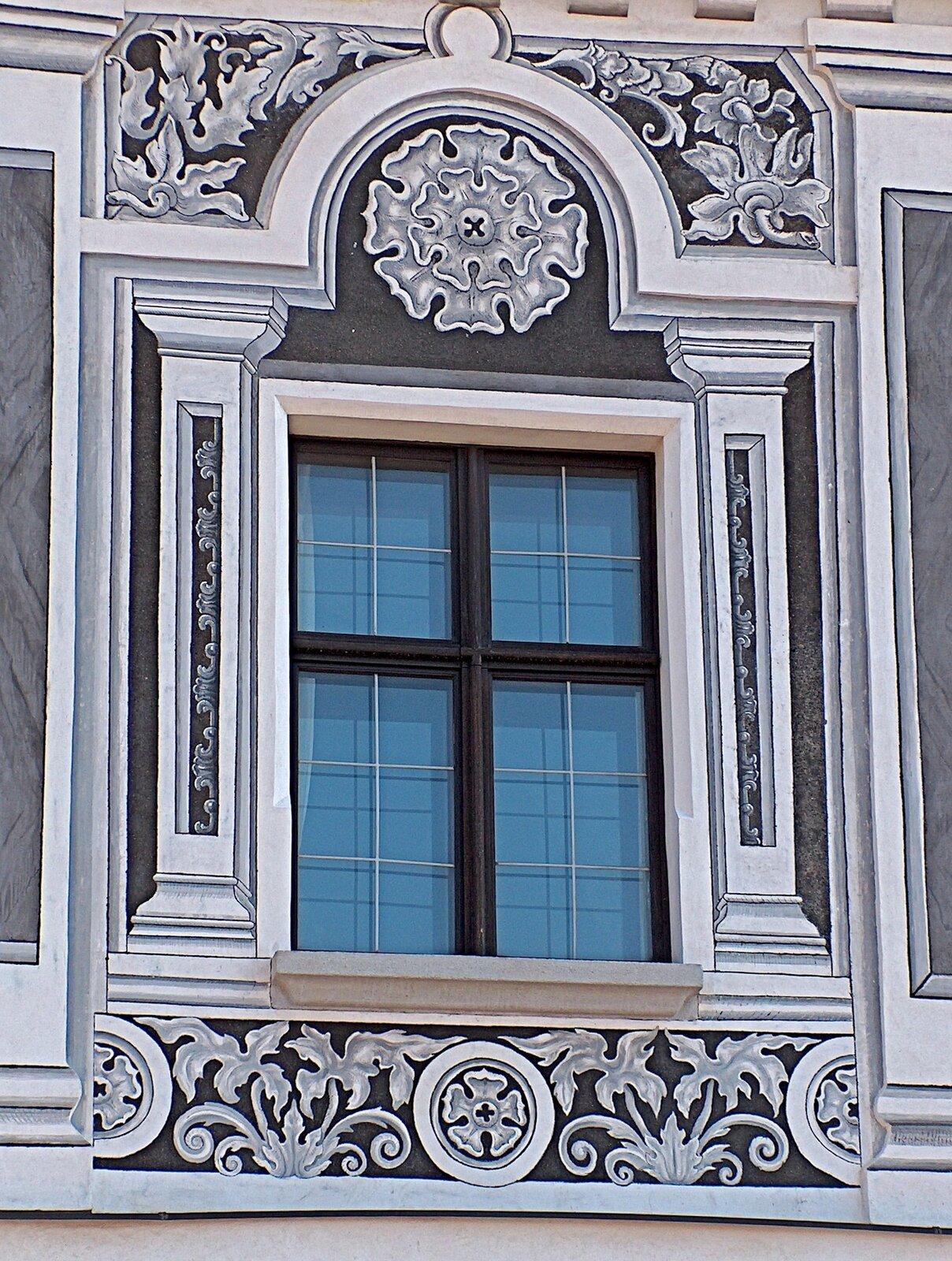 Ilustracja przedstawia sgraffito, będące dekoracją wokół okna. Po bokach są to filary, na górze - okrągły wieloliść, nad którym znajdują się ornamenty roślinne. Podobne motywy znajdują się pod oknem. Dekoracja jest symetryczna, wykonana wkolorze jasnoszarym na ciemnoszarym tle.