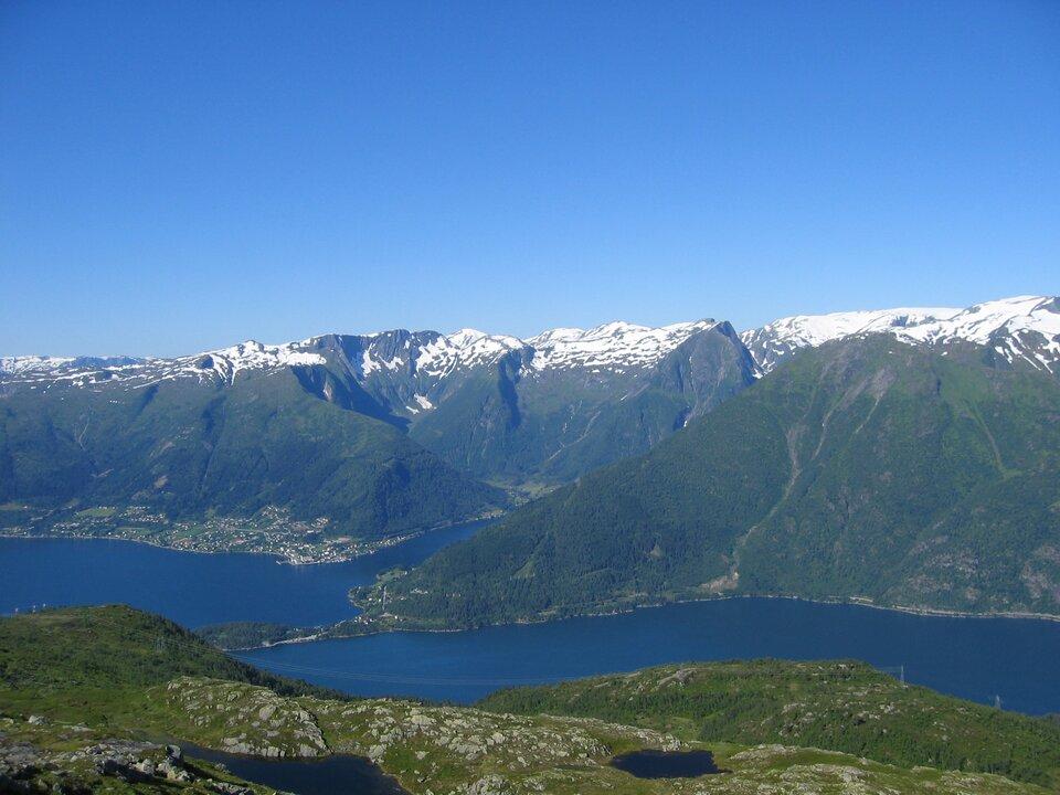 Na zdjęciu pasmo górskie, stoki porośnięte lasami, szczyty płaskie, ośnieżone, wdolinie zbiornik wodny.