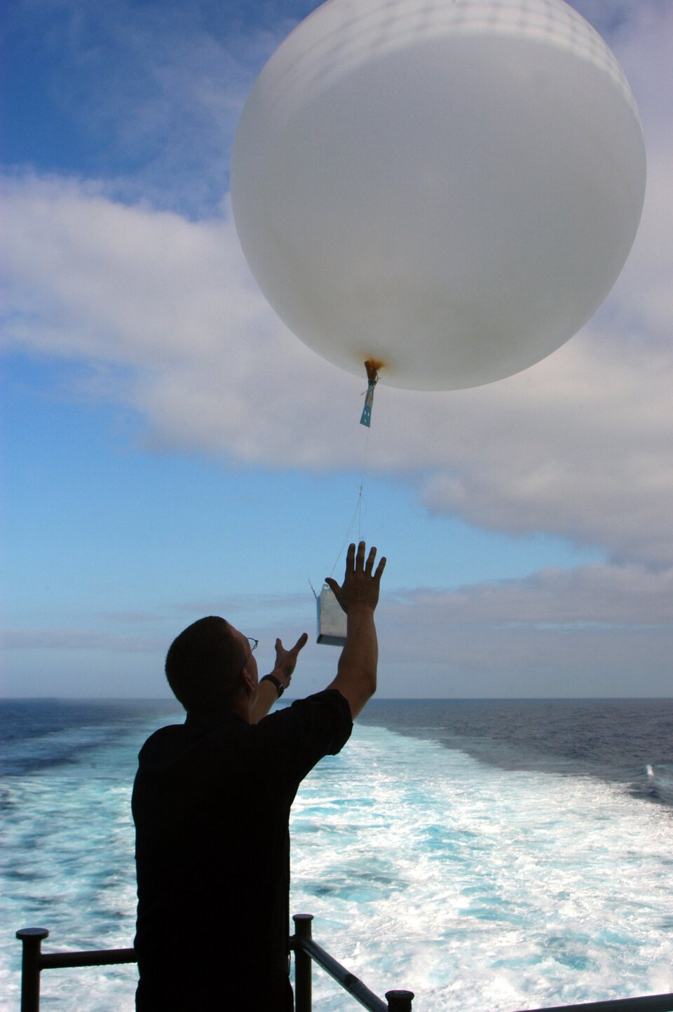 Zdjęcie przedstawia balon meteorologiczny. Niewielki balon ma kształt kuli ośrednicy około dwóch metrów. Pod balonem podwieszona jest skrzynka zprzyrządami służącymi do pomiaru składników pogody.