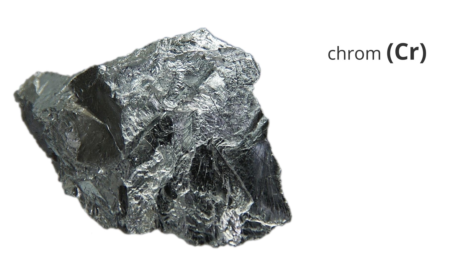 Zdjęcie przedstawia kawałek metalicznego chromu. Obok widnieje napis chrom ijego symbol Cr.