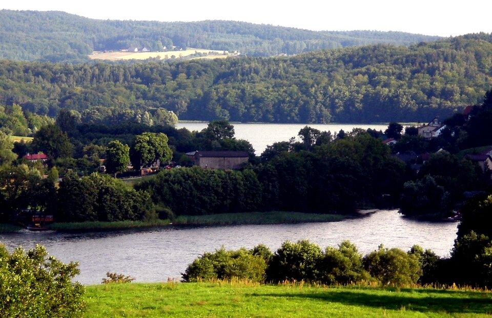 Na zdjęciu dwa jeziora położone wlekko pofalowanym, zalesionym terenie. Gdzieniegdzie zabudowania.