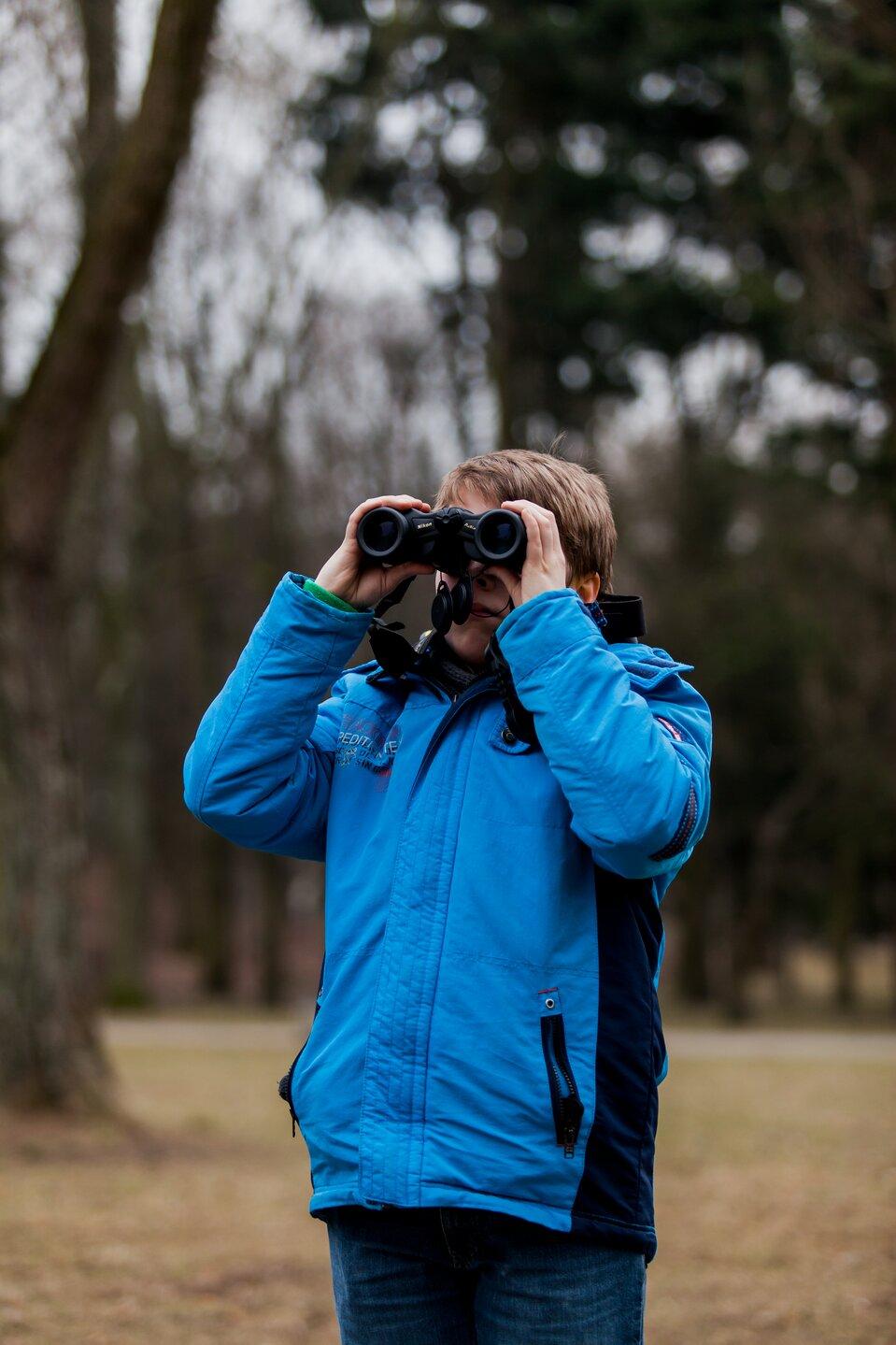 Fotografia młodego człowieka wterenie patrzącego przez lornetkę.