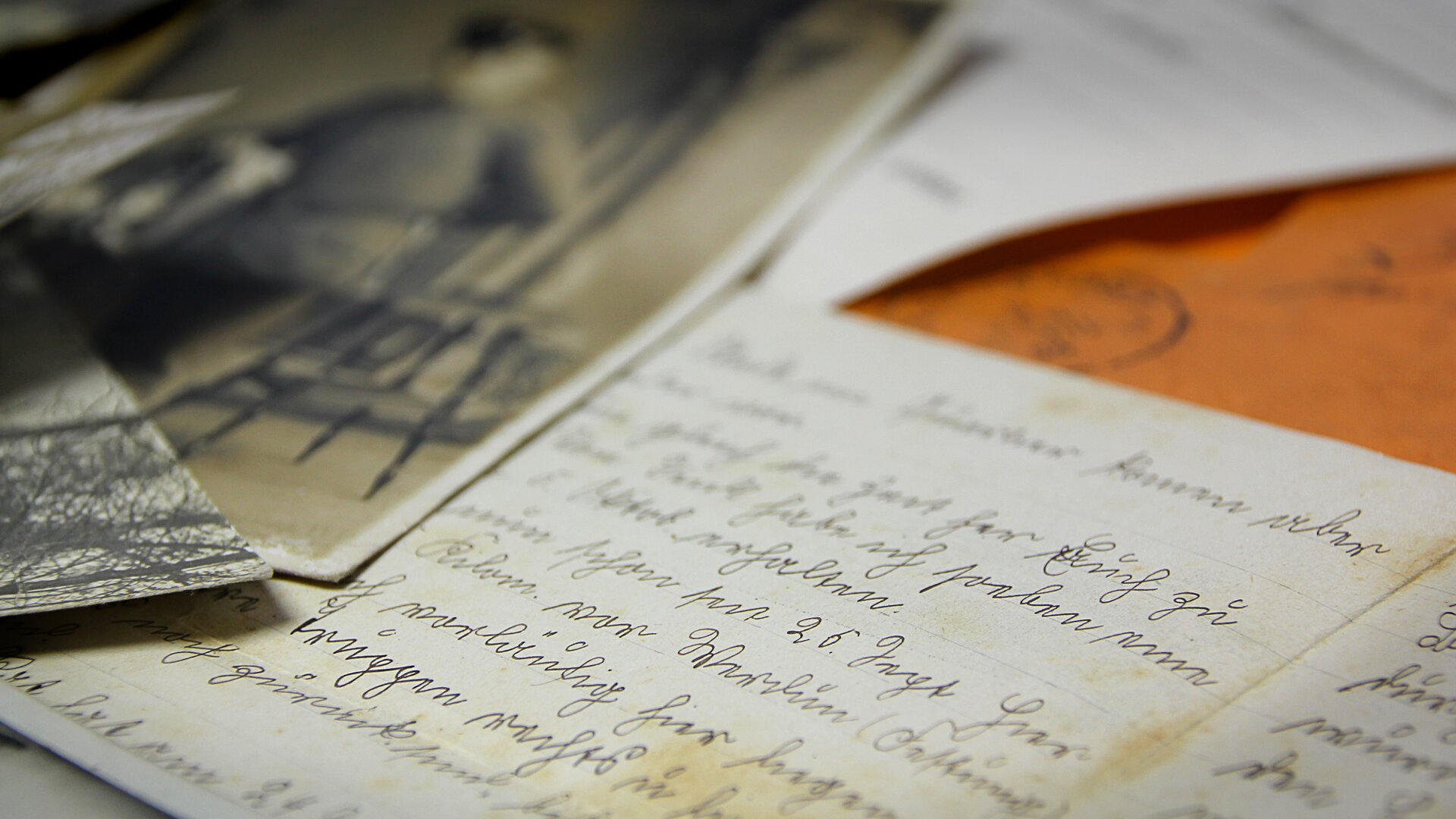 Zdjęcie przedstawia list napisany ręcznie. Papier jest nieco pożółkły, co może świadczyć otym, że jest to list sprzed wielu lat. Obok niego leży czarno-biała fotografia. Widać na niej zarys człowieka. Stoi wyprostowany. Prawdopodobnie ma na sobie mundur.