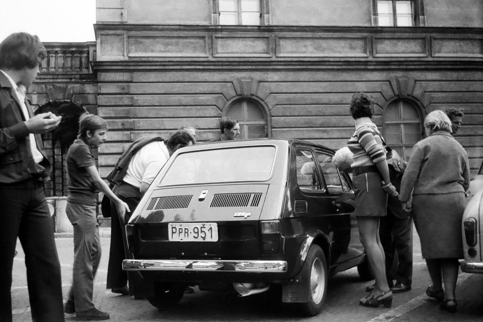 Fotografia czarno-biała przedstawiająca pierwszy samochód maluch zlogo Polskiego Fiata. Tłum ciekawych ludzi oglądających auto zzewnątrz izaglądających do środka przez szybę.