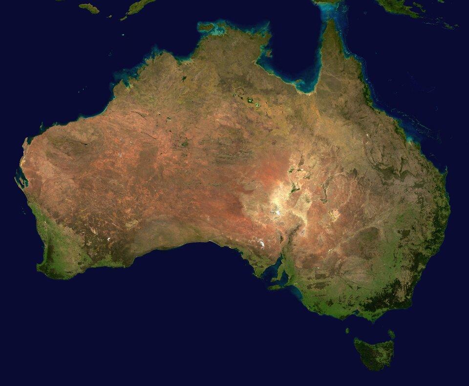 Na zdjęciu satelitarnym kontynent Australii, widoczne tereny zielone nad brzegiem morza ibrunatne oraz żółte wewnątrz kontynentu. Rozczłonkowana linia brzegowa na wschodzie kontynentu.