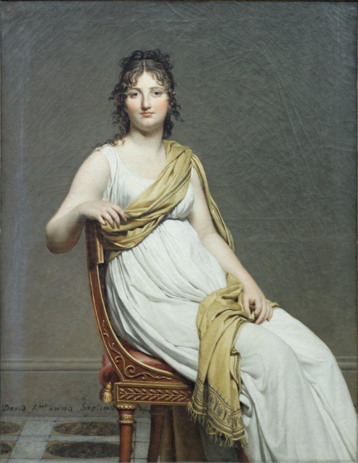 """Ilustracja przedstawia obraz olejny """"Portret Monsieur de Lavoisier ijego żony"""" autorstwa Jacques-Louisa Davida. Kompozycja ukazuje siedzącą damę wbiałej, prostej sukni odrobnych fałdach. Postać owinięta jest jasno-beżową draperią, która spływa wąskim pasmem zlewego ramienia poprzez piersi do prawego boku. Część beżowej tkaniny leży również na jej kolanach. Kobieta siedzi na odwróconym bokiem, brązowym krześle ze złotymi zdobieniami. Jej prawa ręka jest swobodnie ułożona na oparciu, natomiast lewa spoczywa na kolanach. Głowa postaci skierowana jest wkierunku odbiorcy. Lekko uśmiechniętą twarz zdużymi, ciemno-brązowymi oczami izaróżowionymi policzkami wieńczą ciemne, kręcone włosy opadające na ramiona. Dama ustawiona jest we wnętrzu, na tle szarej ściany. Udołu obrazu, znajduje się podłoga zszaro-beżową terakotą wykończoną wzorem odużych, brązowych kach. Obraz wykonany jest zdużą dbałością owierne odwzorowanie natury. Statyczna kompozycja utrzymana jest wwąskiej, szaro-beżowej gamie barw."""