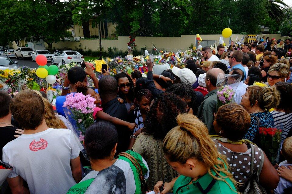 Na zdjęciu tłum przed ogrodzeniem, na którym wiszą balony, flagi ikwiaty.