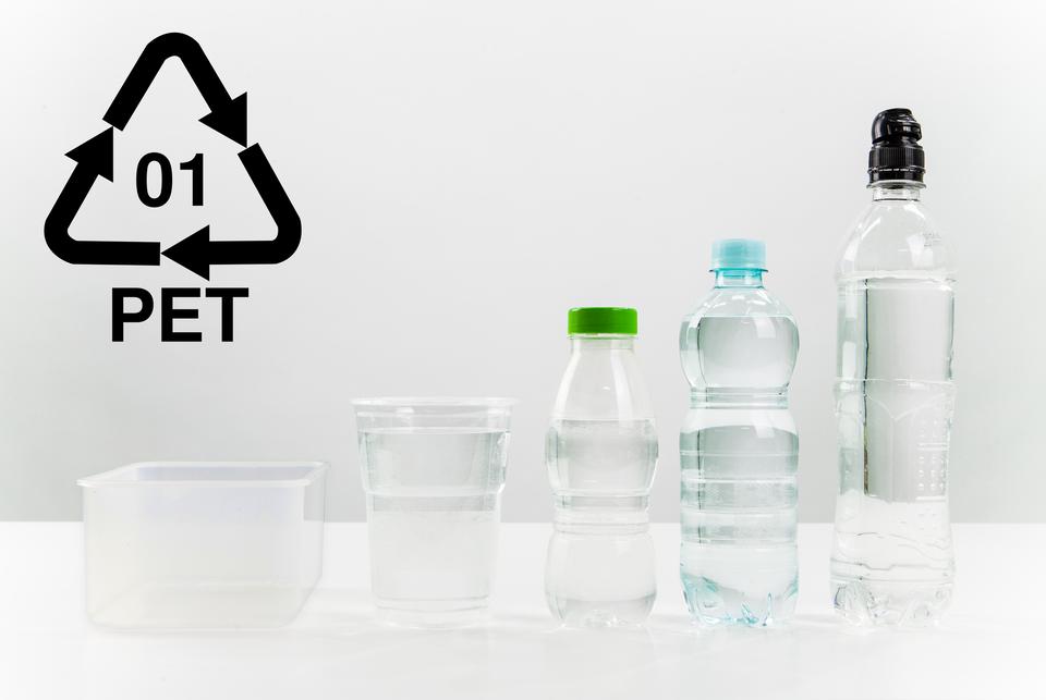 Fotografia kilku opkowań PET: od butelki do pudełka. Wlewym górnym rogu zdjęcia znak graficzny PET