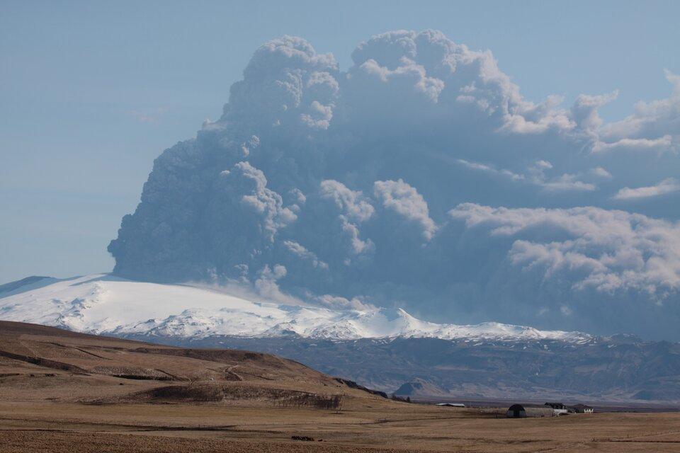 Ośnieżone pasmo górskie, ogromne kłęby czarnego dymu. Na pierwszym planie rozległy pusty teren pozbawiony roślinności.