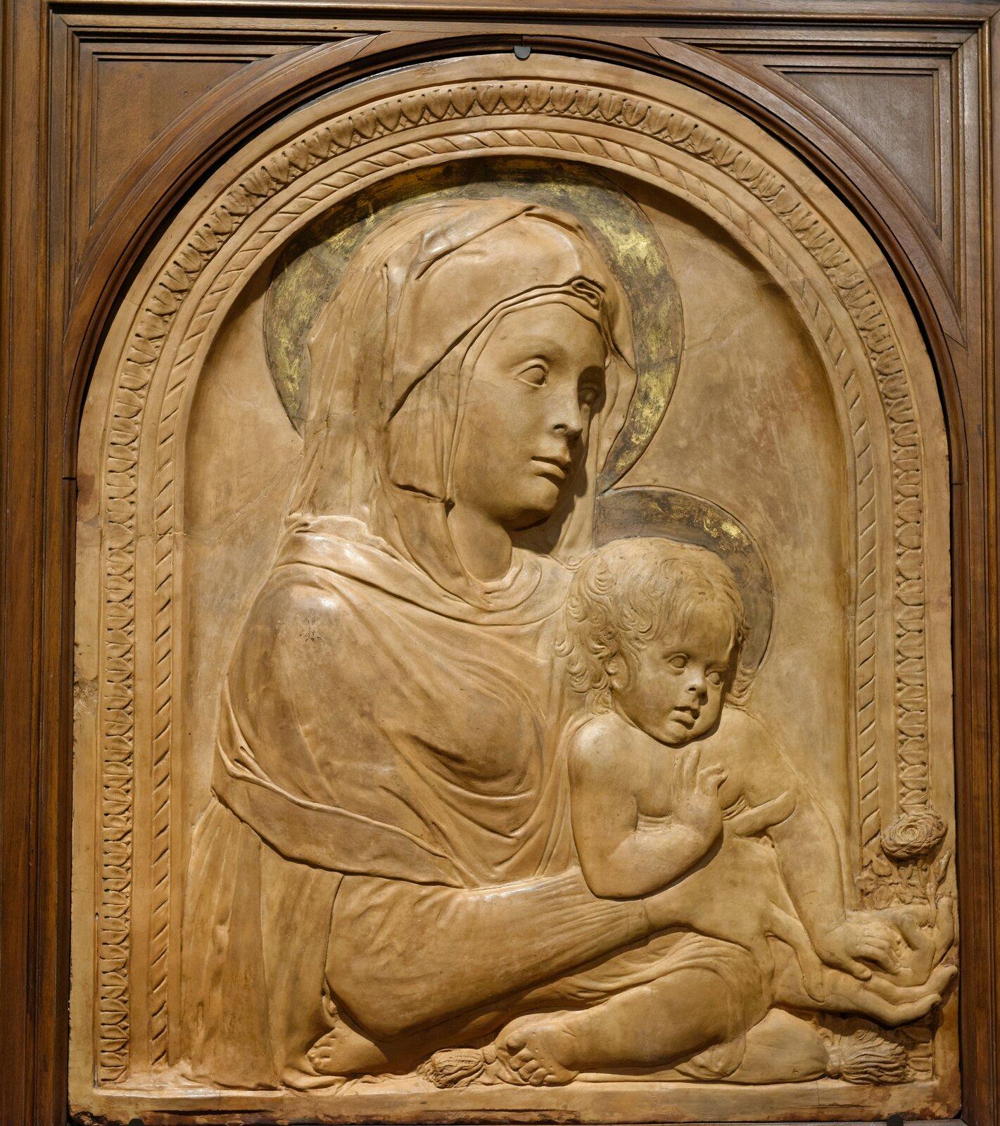 """Ilustracja przedstawia płaskorzeźbę wdrewnie autorstwa Donatella """"Madonna zDzieciątkiem"""". Rzeźba ta przedstawia Marię trzymającą siedzącego na poduszce Jezusa. Głowy postaci otoczone są nimbem. Kobieta ubrana jest wszaty oraz kaptur zakrywający głowę. Wokół nich znajduje się rzeźbione, półkoliste obramienie."""