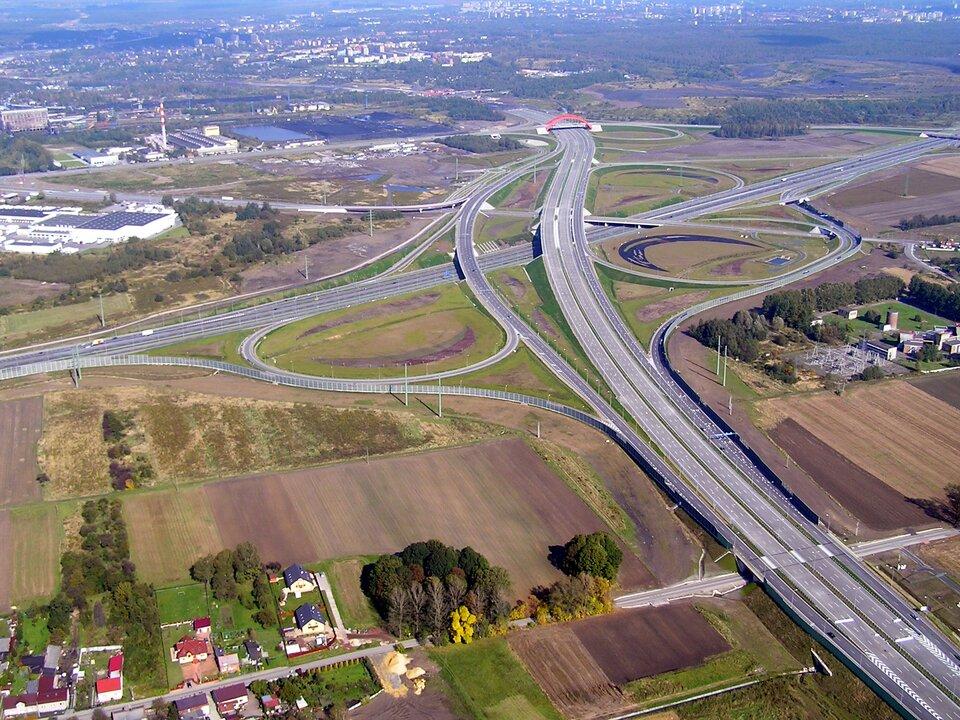 Na zdjęciu lotniczym węzeł drogowy – bezkolizyjne krzyżowanie się dróg na różnych poziomach wpłaskim terenie na przedmieściach dużego miasta na drugim planie.