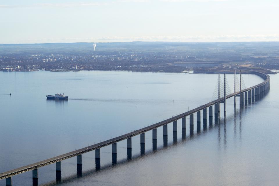 Zdjęcia przedstawiające przykłady budowli wzniesionych przez ludzi, służących do pokonywania przeszkód terenowych.Fotografia długiego, przęsłowego mostu łączącego dwa odległe brzegi szerokiej rzeki.