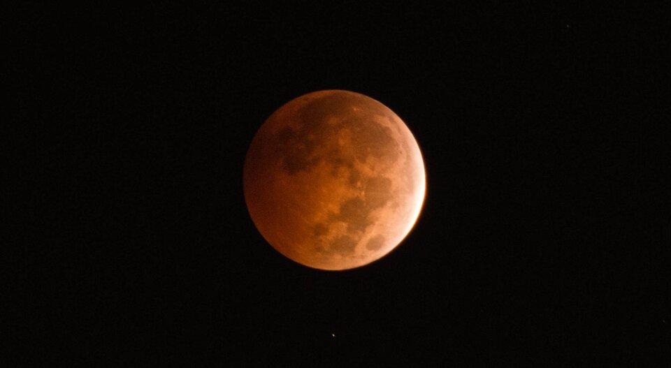 Księżyc wmomencie bliskim całkowitego zaćmienia. Jest widoczny ale przybiera barwę brunatno-czerwoną