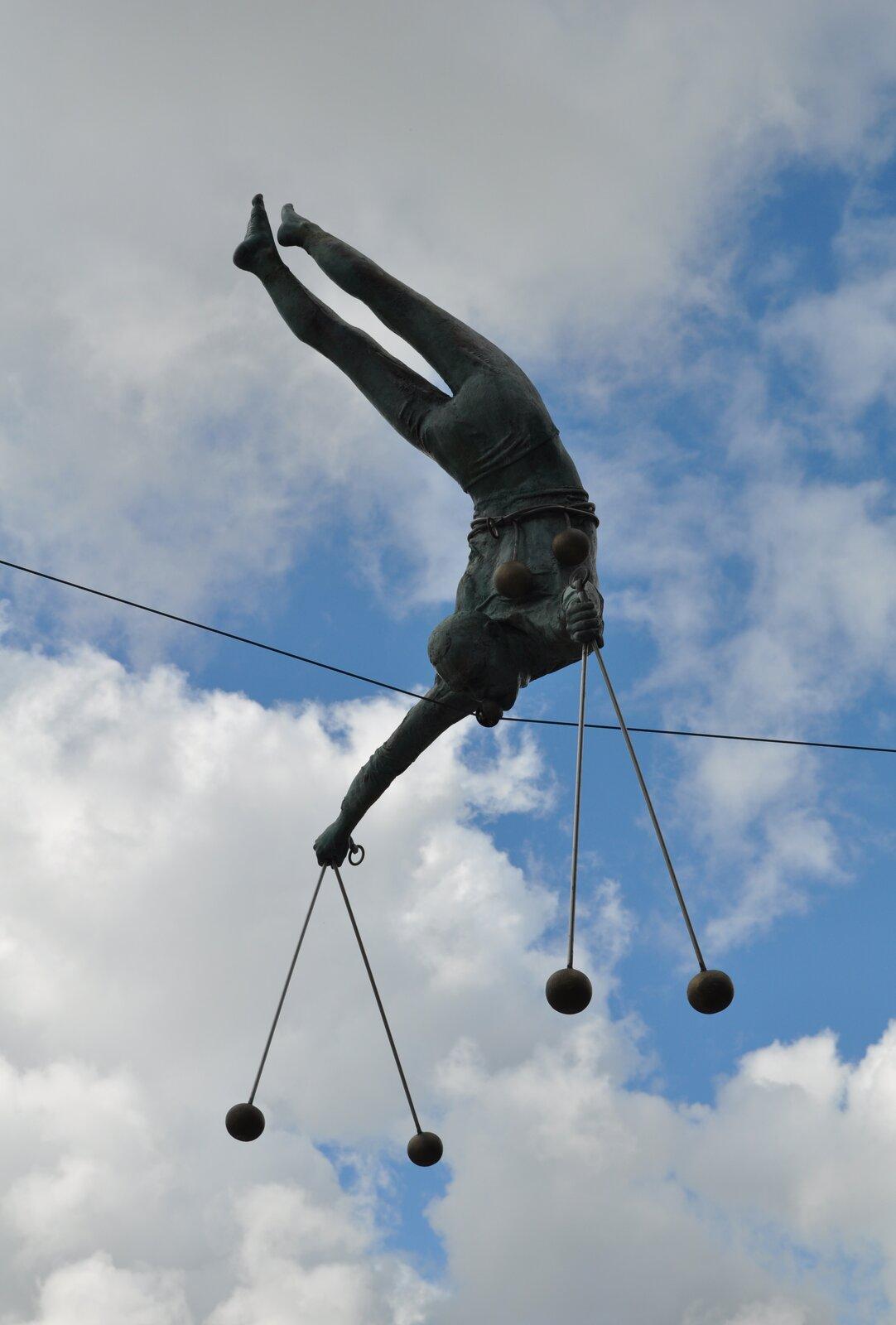 """Ilustracja przedstawia rzeźbę Jerzego Jotki Kędziory pt. """"Click Clack"""". Dzieło przedstawia akrobatę wykonującego sztuczki. Stoi on na głowie na linie. Zobu rąk zwisa mu po parze kulek na sznurkach."""
