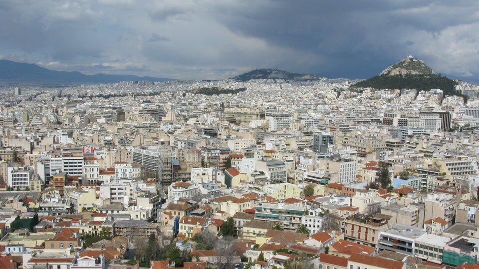 Na zdjęciu bardzo gęsta zabudowa miejska. Wtle pośród budynków dwa zalesione szczyty.
