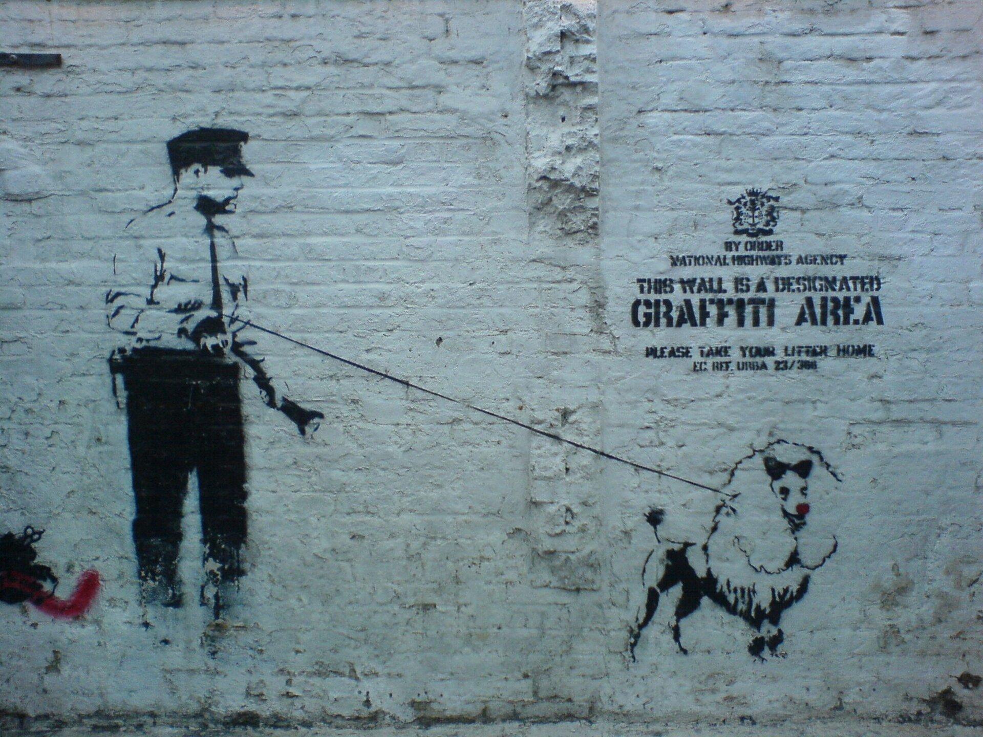 Ilustracja przedstawia czarno-biały street art Banksy'ego wykonany techniką szablonu. Ukazuje Pies zfutrem wokół szyi stoi nieruchomo, ma czerwony nos. Po prawej stronie grafiki ukazany jest napis: GRAFFITI AREA.