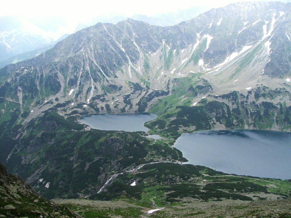 Na ilustracji wysokie góry. Na pierwszym planie dwa zbiorniki wodne wregularnym, okrągłym kształcie.