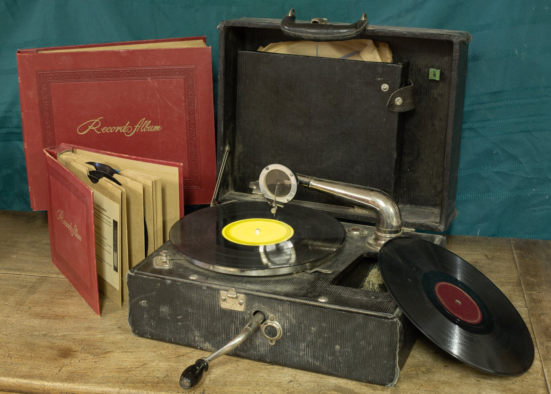Ilustracja przedstawia zdjęcie martwej natury. Na drewnianym blacie ustawiony jest czarny, stary gramofon wformie walizki. Górna klapa jest otwarta, awjego wnętrzu widoczna jest czarna winylowa płyta zżółtym środkiem, nad którą spoczywa ramię zokrągłą główką iigłą. Zprzedniej ścianki gramofonu wystaje metalowa korbka, natomiast zprawej strony leży oparta ojego brzeg, druga, czarna płyta Po lewej stronie kadru stoją ustawione wpionie dwa, oprawione na czerwono albumy. Większy, zamknięty opiera się ościanę. Przed nim stoi mniejszy, lekko rozchylony. Martwa natura ustawiona jest na tle ciemno-błękitnej ściany.
