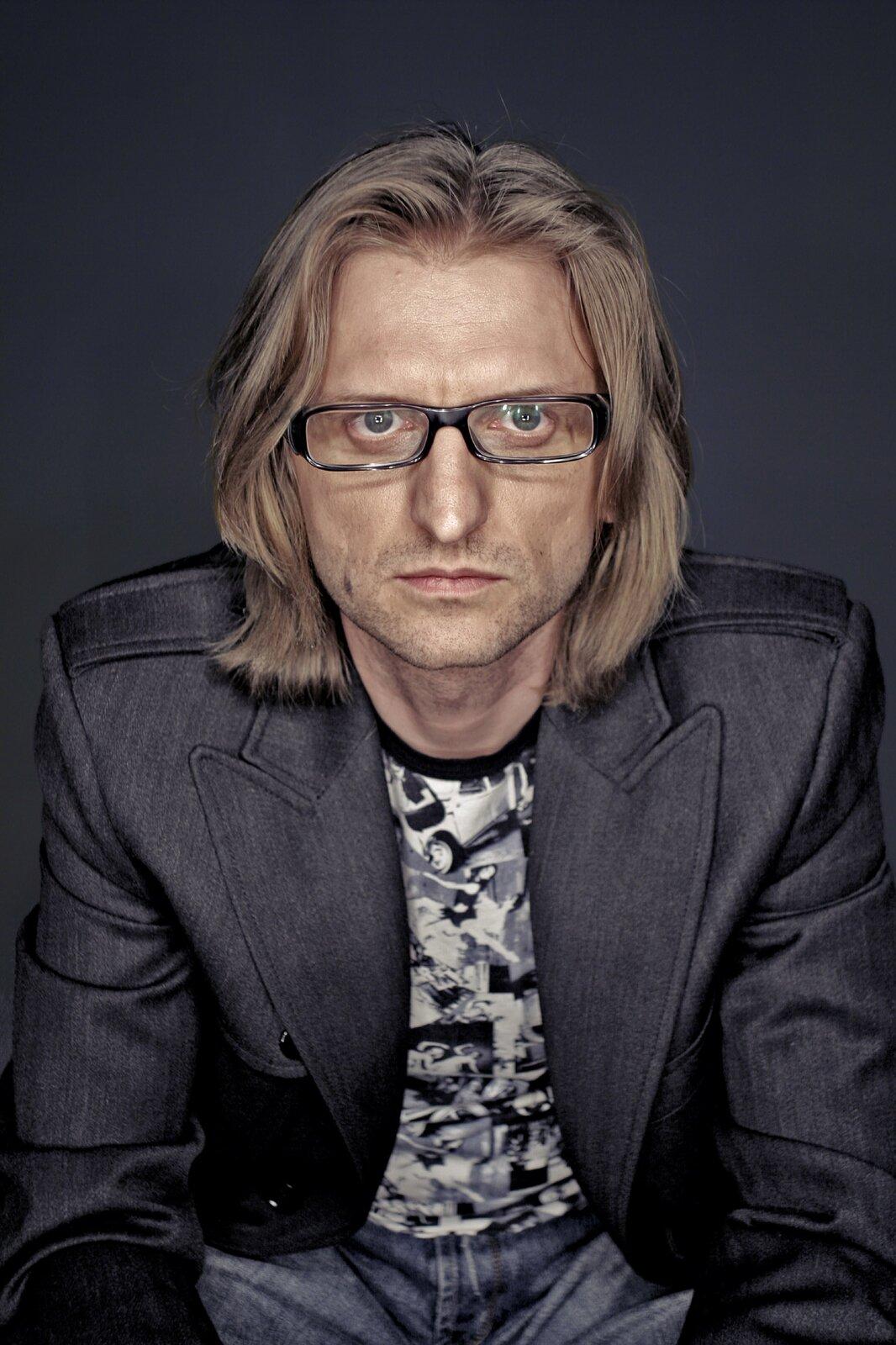 Ilustracja przedstawia zdjęcie portretowe polskiego muzyka Leszka Możdżera autorstwa Nikodema Krajewskiego.