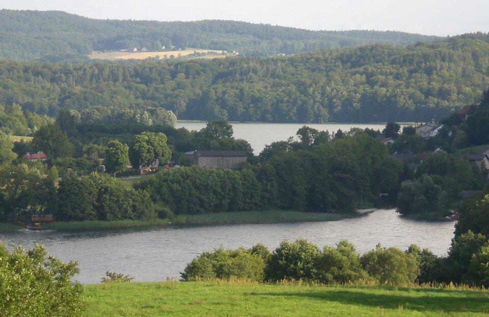 Na zdjęciu kilka jezior wlekko pofałdowanym, zalesionym terenie. Gdzieniegdzie zabudowania.