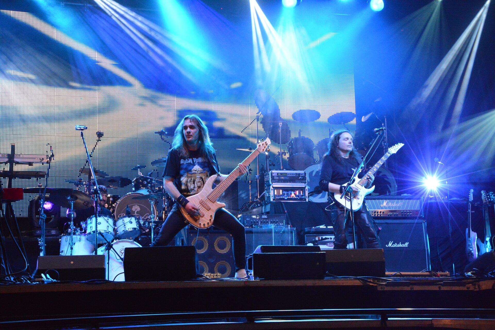 Ilustracja przedstawia koncert rockowy. Widocznych jest dwóch mężczyzn grających na gitarach. Wtle widoczna jest perkusja oraz głośniki.