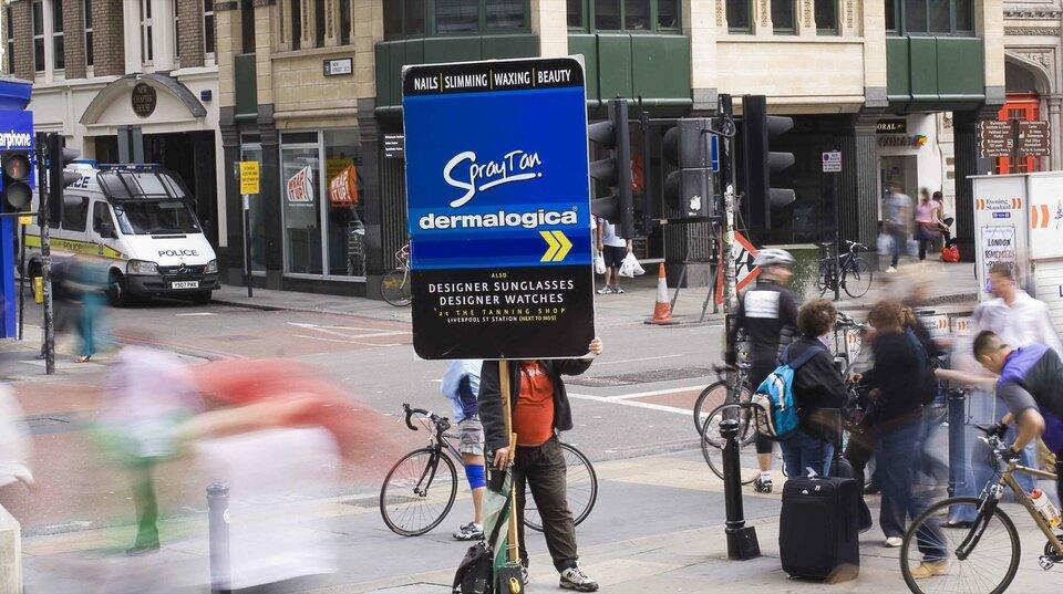 Zdjęcie przedstawia ruchliwą ulicę wcentrum Londynu. Róg przy skrzyżowaniu dwóch ulic oruchu pieszo rowerowym. Wcentralnej części kadru stoi człowiek trzymający dużą tablicę reklamującą usługi salonu kosmetycznego. Twarz człowieka zasłonięta tablicą, ubranie stanowią brązowe spodnie, czerwony t-shirt iczarna rozpięta kurtka. Dookoła trwa normalna krzątanina podkreślona fotograficznym zabiegiem rozmycia wszystkich poruszających się obiektów wkadrze. Sportretowany człowiek ukazany jest ostro, co oznacza, że nie wykonuje żadnych gwałtownych ruchów.