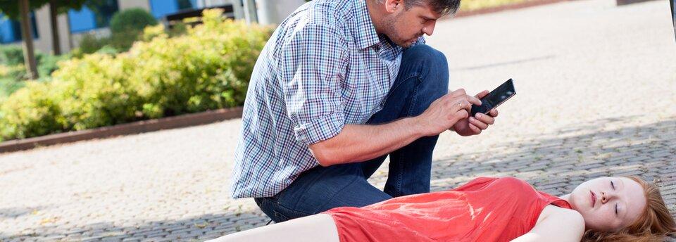 Kolorowe zdjęcie przedstawia leżącą na ulicy nieprzytomną młodą dziewczynę iklęczącego obok niej mężczyznę, który wybiera na telefonie komórkowym numer. Dziewczyna, ubrana wczerwoną letnią sukienkę, ułożona jest na wznak, ma zamknięte oczy, głowę przechyloną lekko wlewą stronę.
