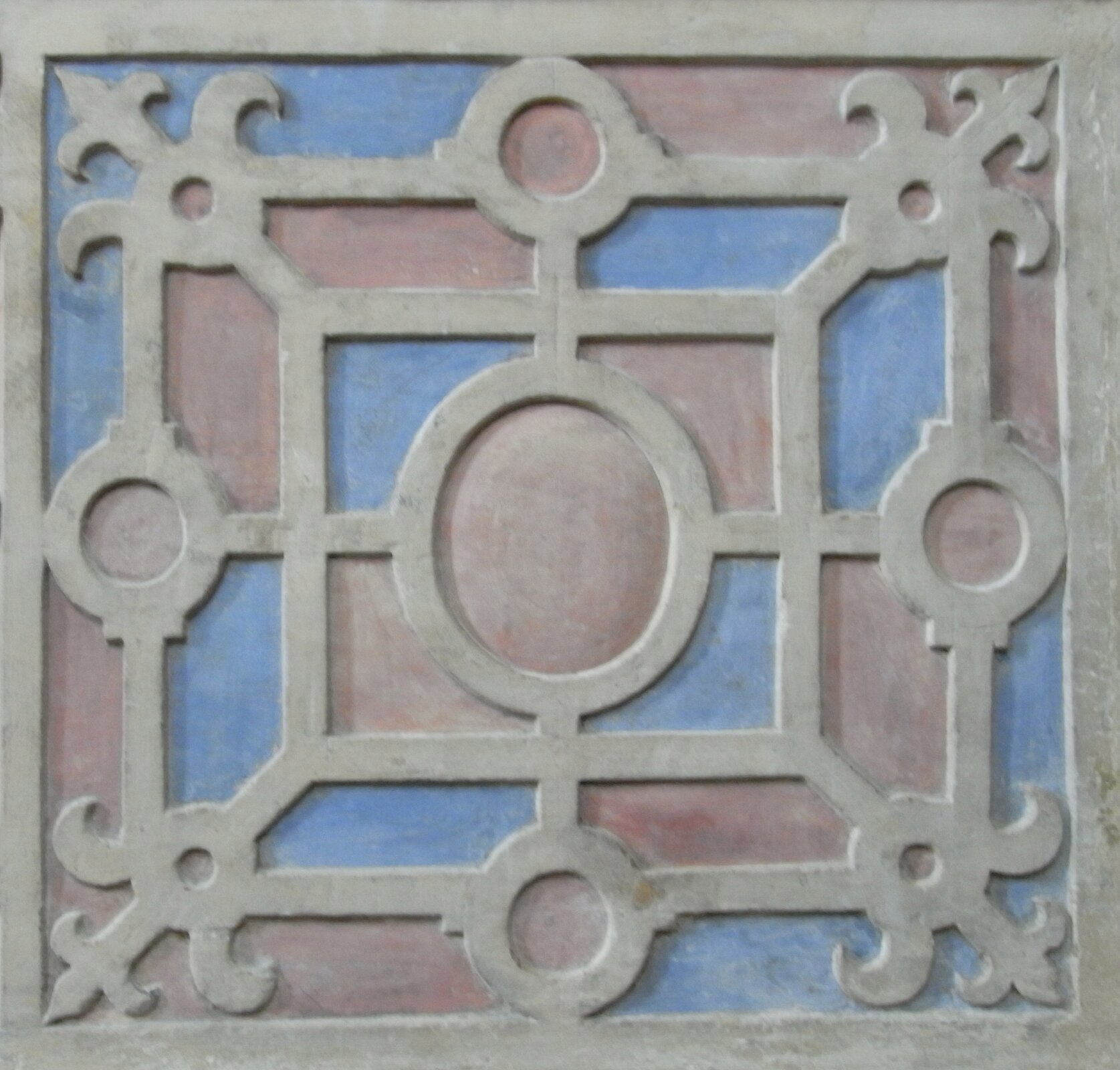 Ilustracja przedstawia ornament okuciowy. Ornament wykonany jest wkształcie kwadratu. Wjego centralnym punkcie znajduje się okrąg. Dookoła niego naprzemiennie widoczne są okręgi oraz krzyże zzaokrąglonymi końcami. Wszystkie elementy połączone się liniami.