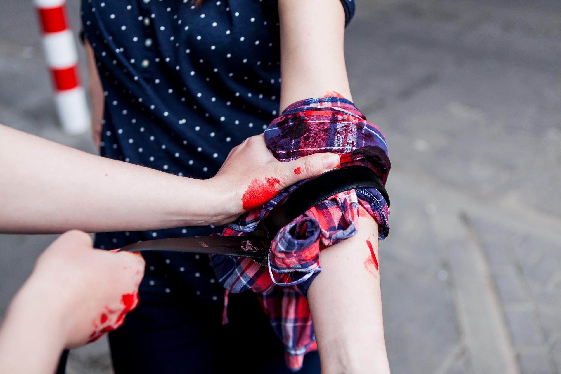 Zbliżenie sceny udzielania pierwszej pomocy przy użyciu dostępnych pod ręką przedmiotów. Zdjęcie przedstawia zakrwawioną rękę poszkodowanej osoby oraz dłonie świadka udzielającego pierwszej pomocy poprzez założenie opatrunku zkraciastej koszuli unieruchomionej na miejscu paskiem od spodni. Na rękach poszkodowanego iratownika, atakże na koszuli widać ślady krwi.