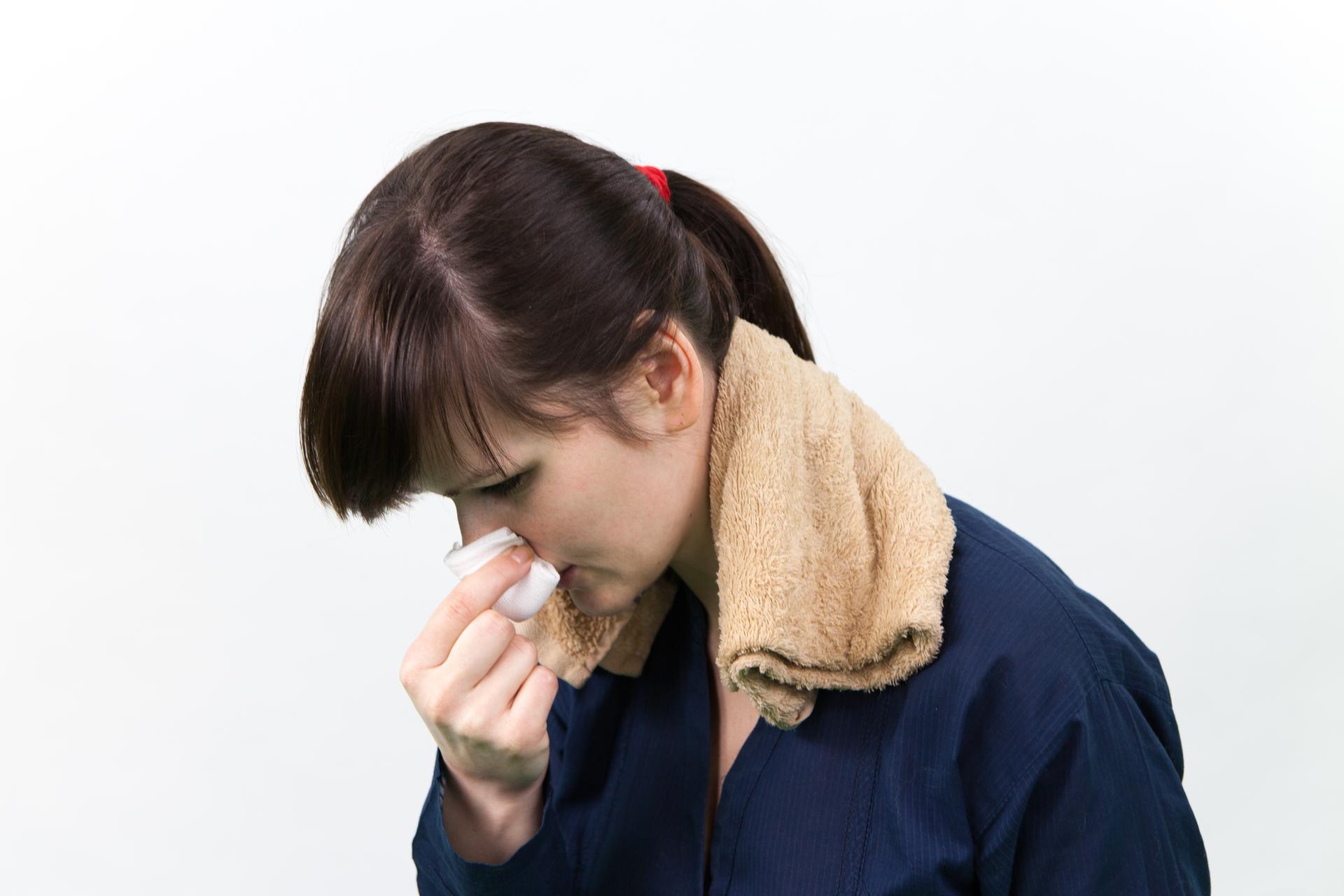 Zdjęcie człowieka zpochyloną głową, gazą przy nosie, na karku ma położony mokry ręcznik.