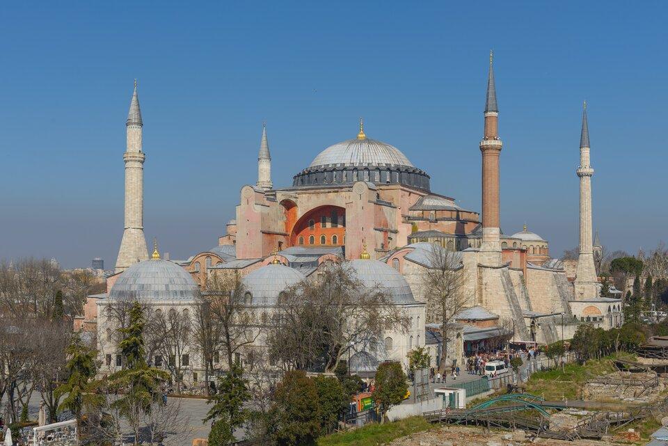 Współczesne zdjęcie meczetu Hagia Sofia. Centralny budynek przykryty kopułą otoczony jest mniejszymi zabudowaniami również mającymi dachy wformie kopuł, awokół tego stoją cztery okrągłe, ostro zakończone wieże minaretów.