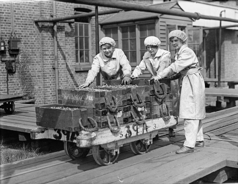 Kobiety pchające wagon złuskami do amunicji Źródło: Lewis, Kobiety pchające wagon złuskami do amunicji, 1918, Imperial War Museums, domena publiczna.