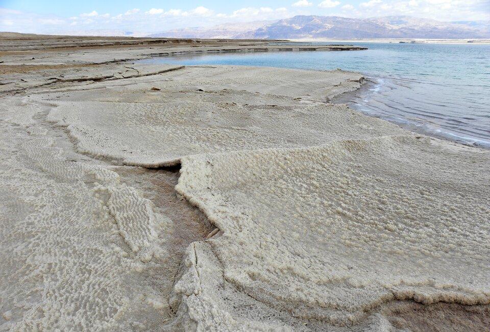 Na zdjęciu brzeg morza, na plaży wykwity soli. Wtle góry.