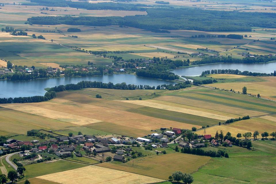 Fotografia wykonana zlotu ptaka ukazuje jeziora Pojezierza Wielkopolskiego. Wokół jezior widoczne liczne pola iłąki.