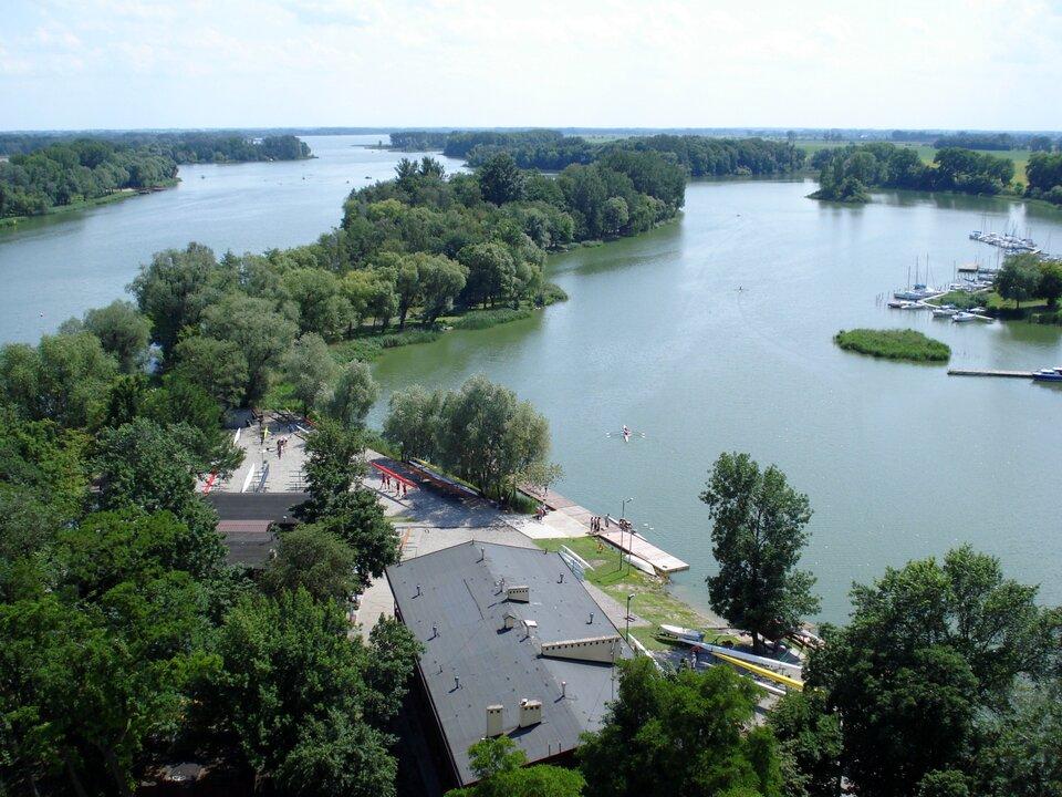 Na zdjęciu długie, wąskie, kręte jezioro. Zabudowania, drzewa.