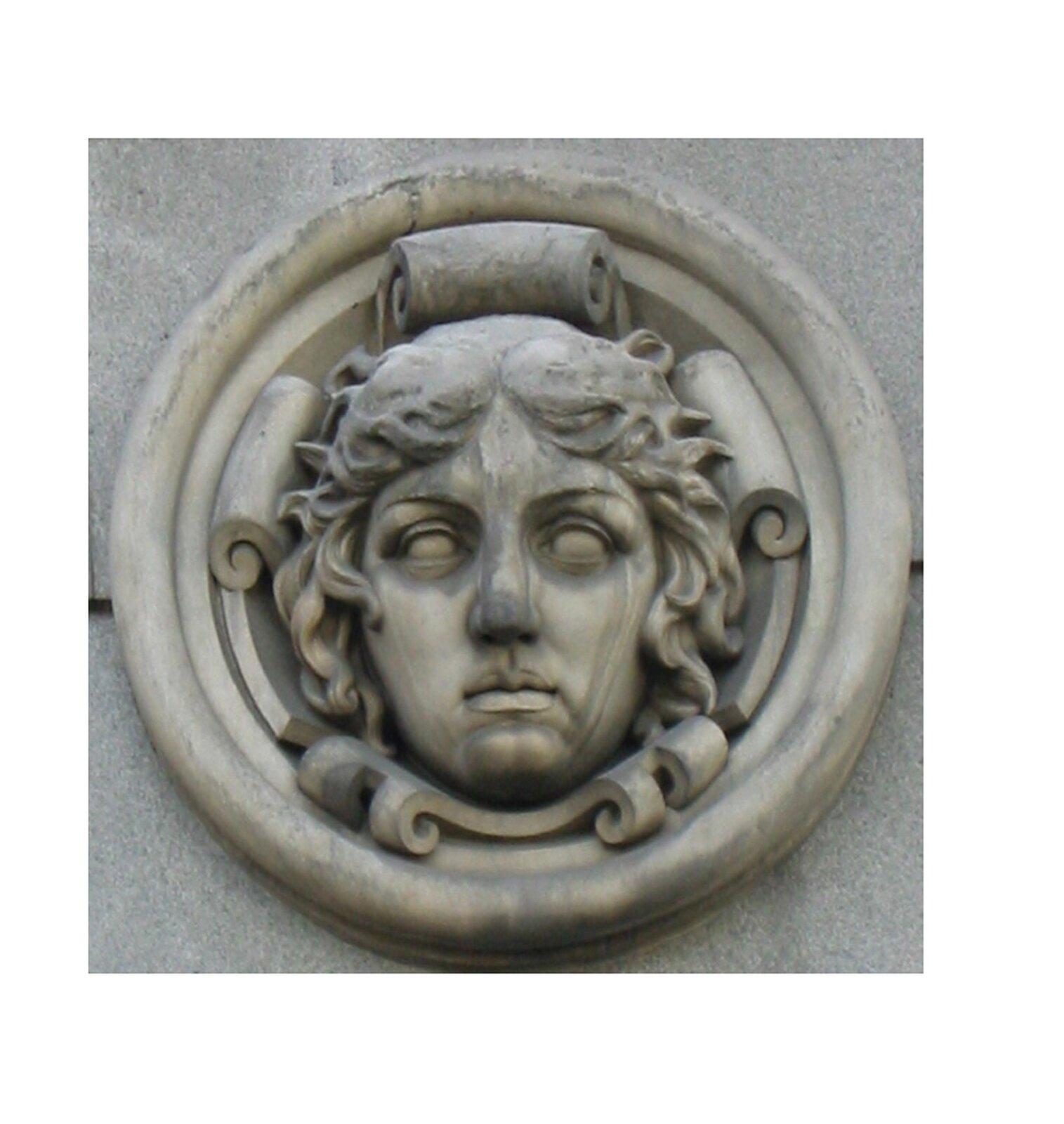 Ilustracja przedstawia ornament – medalion. Ten element dekoracyjny przedstawia twarz młodej kobiety zkrótkimi kręconymi włosami. Element ten jest okrągły iznajduje się prawdopodobnie na ścianie.