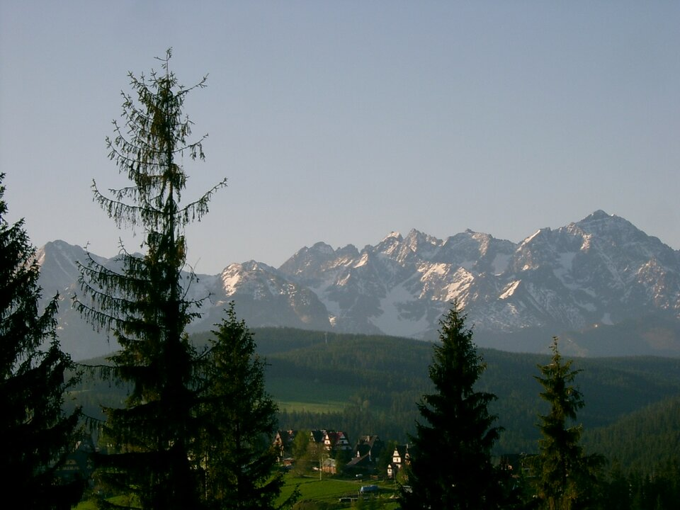 Na zdjęciu wysokie, ośnieżone pasmo górskie, na pierwszym planie teren zabudowany.