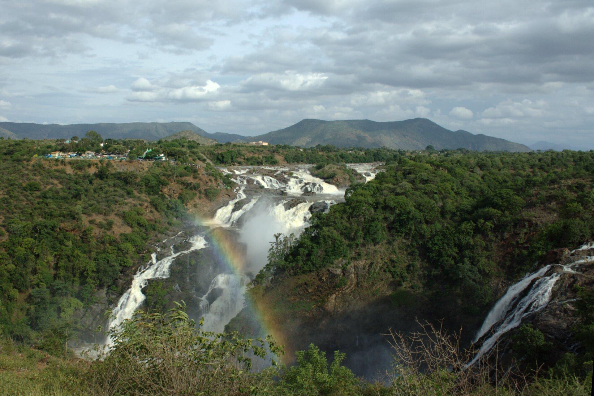 Na zdjęciu rozległy płaski zalesiony teren, płynąca rzeka, wodospad. Wtle wysokie góry.
